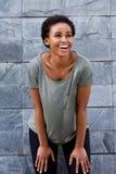 Chłodno młoda murzynka ono uśmiecha się z koszulką przeciw szarości ścianie Obraz Stock