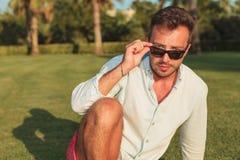 Chłodno młody człowiek bierze daleko jego okulary przeciwsłonecznych podczas gdy siedzący Zdjęcia Royalty Free