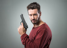 Chłodno młody człowiek trzyma pistolet obrazy stock
