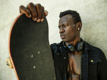 Chłodno odosobniony portret młody atrakcyjnego i ufnego modnisia czarnego afrykanina Amerykański mężczyzna opiera na ulicy ściany zdjęcie royalty free