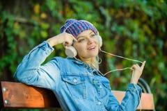 Chłodno ostra dziewczyna cieszy się muzykę w hełmofonach plenerowych Dziewczyna słucha muzykę w parku Melodia dźwięk i mp3 Fan mu obrazy royalty free