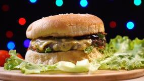 Chłodno piękny świeży soczysty gotujący hamburger wiruje na turntable przeciw tłu kolorowi rozmyci światła zbiory