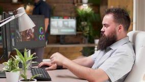 Chłodno przyglądający brodaci videographer lub kolorysty wors na projekcie zbiory wideo
