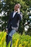 Chłodno 40s biznesmen opowiada z telefonem komórkowym w zieleń parku Zdjęcia Royalty Free
