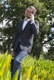 Chłodno 40s biznesmen opowiada z telefonem komórkowym w zieleń parku Fotografia Royalty Free