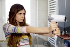 Chłodno silna kobieta wskazuje cios suszarkę jak pistolet Zdjęcia Royalty Free