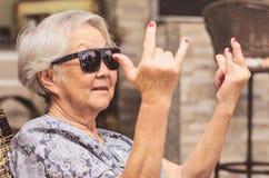Chłodno stara dama, jest ubranym okularów przeciwsłonecznych robić kołysa znaka obraz royalty free