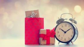 Chłodno torba na zakupy, czarny budzik i piękni prezenty na, Obraz Royalty Free