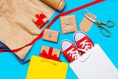 Chłodno torba na zakupy, czerwoni gumshoes i piękny prezent blisko rzeczy, Fotografia Royalty Free