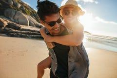 Chłopak daje piggyback przejażdżce dziewczyna przy plażą fotografia royalty free
