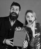 Chłopak daje prezentowi jego dziewczyna Dziewczyna i brodaty mężczyzna z zdziwionymi twarzami i prezenta pudełkiem zdjęcia royalty free