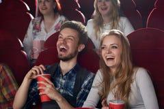 Chłopak i dziewczyna zaskakiwaliśmy uśmiechniętego dopatrywania komediowego film przy kinem zdjęcia royalty free