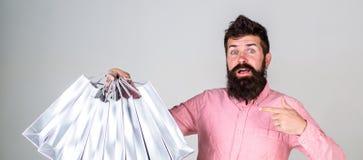Chłopak niesie udziały torba na zakupy i wskazuje przy torbami Mężczyzna z brodą niesie wiązkę torba na zakupy, popielatą obraz royalty free