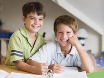 chłopak robi swoje zadanie domowe razem dwa młode Obrazy Royalty Free