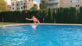 Chłopiec łapie balowego doskakiwanie w basen zbiory