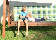 Chłopiec łaskotania dziewczyna na drewnianej huśtawce Zdjęcia Stock