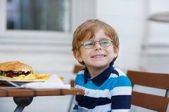 Chłopiec łasowania fast food: francuza hamburger i dłoniaki fotografia stock