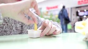 Chłopiec łasowania fast food w sądzie i maczanie Francuskich dłoniakach w plastikowym rozporządzalnym zbiorniku z kumberlandem re zbiory