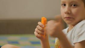Chłopiec łasowania marchewka na kanapie zbiory