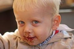 Chłopiec łasowania ono uśmiecha się i ciastko. Zakończenie Obrazy Royalty Free