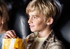 Chłopiec łasowania popkorn Podczas gdy Oglądający film Zdjęcie Royalty Free