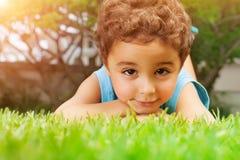 Chłopiec łgarski puszek na zieleni polu Fotografia Stock