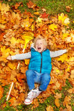 Chłopiec śmia się i kłaść na jesień liściach z świntuchem fotografia stock