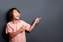 Chłopiec śmia się i wskazuje przy kopii przestrzenią Zdjęcie Stock