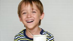 Chłopiec śmia się przy kamerą Dziecko siedzi przy stołem i je jogurt Szcz??liwe emocje dziecka t?a karmowy makaronowy surowy biel zbiory