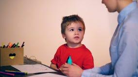 Chłopiec angażuje w rysunku z nauczycielem na szarym tle koncepcja uczenia się Dziecko w wieku szkolnym w mundurze zbiory wideo