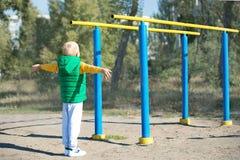 Chłopiec atleta robi ciągnieniu podnosi aktywny tryb życia Dziecko wykonuje ćwiczenia na nierównych barach na ulicie zdjęcia stock