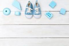 Chłopiec błękita buty i drewniane zabawki na białym drewnianym tle Obrazy Stock