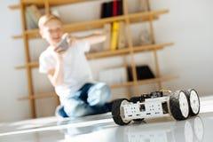 Chłopiec bada jego mechaniczną pojazd zabawkę Fotografia Stock