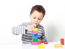 Chłopiec bada jego twórczość góruje z zabawkarskimi elementami budować zdjęcie stock