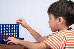 Chłopiec bawić się łączy cztery gier miękką ostrość przy kontakt wzrokowy salowymi aktywność zdjęcie royalty free
