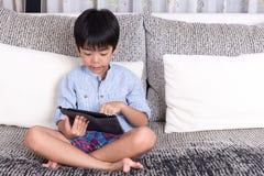 Chłopiec bawić się cyfrową pastylkę Zdjęcia Stock