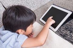 Chłopiec bawić się cyfrową pastylkę Zdjęcia Royalty Free