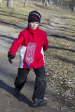 Chłopiec bawić się futbol bitwę w lasowej jesieni Fotografia Stock
