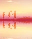 Chłopiec bawić się futbol przy zmierzchem Sylwetki pojęcie Obrazy Royalty Free