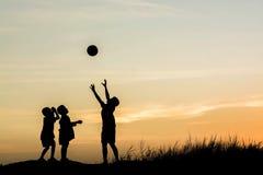 Chłopiec bawić się futbol przy zmierzchem Sylwetki pojęcie Zdjęcie Royalty Free