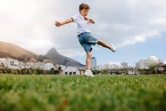 Chłopiec bawić się futbol w parku Zdjęcia Stock