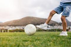 Chłopiec bawić się futbol w parku Obraz Royalty Free
