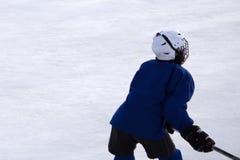 Chłopiec bawić się hokeja na ulicznym łyżwiarskim lodowisku Chłopiec na ulicznym bawić się hokeju obraz royalty free