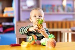 Chłopiec bawić się indoors w domu lub dzieciniec Uroczy dziecko z plastikowymi warzywami i owoc zdjęcie royalty free