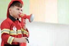 Chłopiec bawić się jako palacz polici zajęcie w dzieciniec klasie, Fotografia Royalty Free