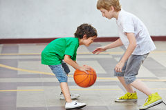 Chłopiec bawić się koszykówkę w szkole obraz stock