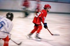 Chłopiec bawić się lodowego hokeja na lodowisku obraz stock
