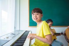 Chłopiec bawić się muzyczną klawiaturę przy szkołą Zdjęcia Royalty Free