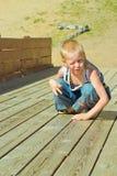 Chłopiec bawić się na drewnianym obruszeniu Zdjęcie Royalty Free