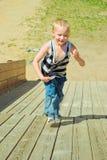 Chłopiec bawić się na drewnianym obruszeniu Zdjęcia Stock